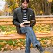 Middle-aged man with a book in autumn park — Stock Photo