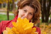 Woman in autumn park with a bouquet of maple leaves — Stock Photo
