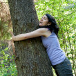 A beautiful middle-aged woman in a forest near an old tree — Stock Photo
