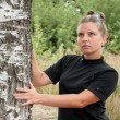 Stock Photo: Russimiddleaged womstands of birch