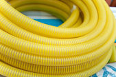 Yellow garden hose for watering, is irregularly wound — Stock Photo
