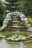 Landscaping - pond with rock slide and waterfall — Stock Photo
