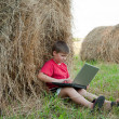 Stock Photo: A boy with a laptop in the field
