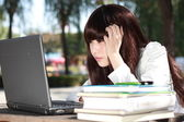 Sta studiando una sorridente studentessa asiatica. — Foto Stock