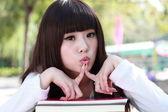 Eine lächelnde asiatische studentin studiert. — Stockfoto