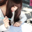 A smiling Asian student is studying. — Foto Stock