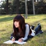 Eine lächelnde asiatische Studentin studiert — Stockfoto