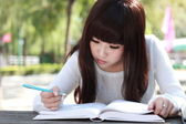 A smiling Asian student is studying. — Стоковое фото