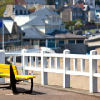 Empty yellow bench at coastline - Stock Photo
