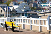 Empty yellow bench at coastline — Stock Photo