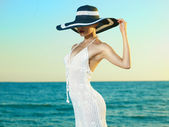 Elegant woman in a hat at sea — Stock Photo