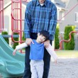 Father helping disabled son at playground — Stock Photo