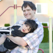 Father helping disabled son to play at playground — Stock Photo