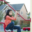 Nine year old girl playing on the bars at playground — Stock Photo