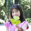 Stock Photo: Ten year old girl holding out large three leaf clover