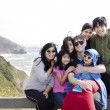 Stock Photo: Multiracial family of seven sitting by Pacific Ocean. Little