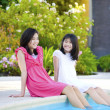 Two young girls sitting by swimming pool, smiling — Stock Photo #7668595