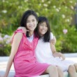 Two young girls sitting by swimming pool, smiling — Stock Photo