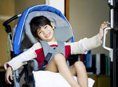 Handsome four year old disabled boy in wheelchair opening front — Stock Photo