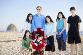 Large family of seven standing on the beach by the ocean — Stock Photo