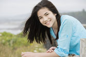 Preteen biracial girl with a beautiful smile, overlooking the oc — Stock Photo