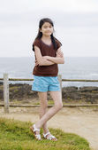 Little nine year old girl posing arms crossed by ocean — Stock Photo