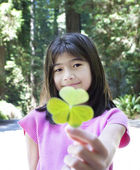 Ten year old girl holding out large three leaf clover — Stock Photo