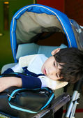 Disabled five year old boy in wheelchair waiting at school — Stock Photo