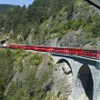 Glacier Express driving over a viaduct into a tunnel — Stock Photo