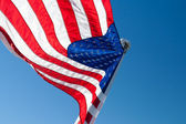 Amerikan arka ışık ile boşaltmak mavi gökyüzü karşı bayraklı — Stok fotoğraf