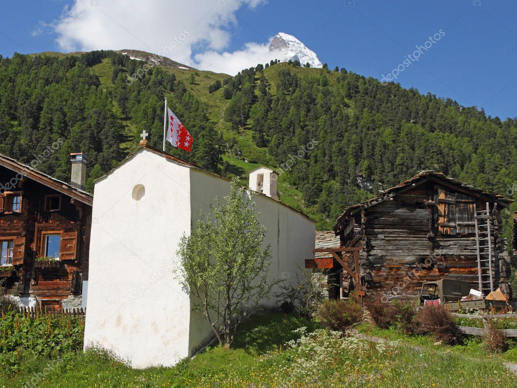 Small swiss village settlement of wooden houses with little white stone church hugh snow covered alpine mountains in Valais, Switzerland — Stock Photo #6890338