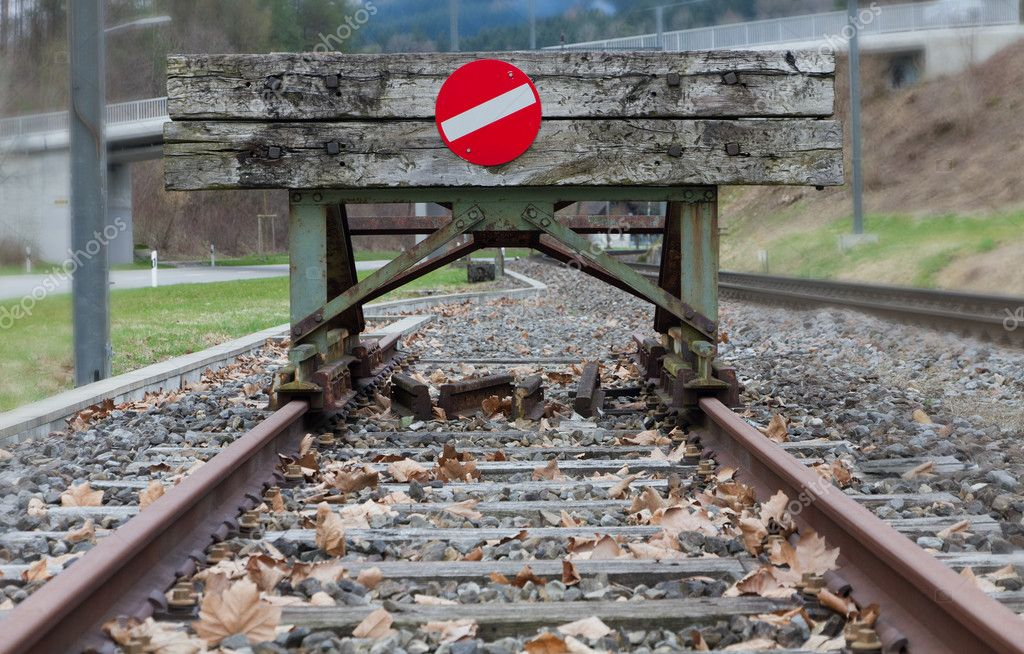 Wooden buffer stop with red stop sign ending rail tracks concept for limit, limitation restrication boundary, prohibited, end , border  Stock Photo #6943841