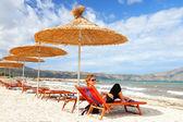 Girl on the beach under straw umbrella — Stock Photo