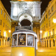 Stock Photo: Lisbon: old yellow tram with triumphal arch, Portugal