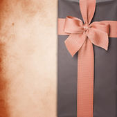 Gift box with ribbon on grunge background — Stock Photo