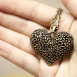 Suspension in a heart-shaped, bronze-colored with a chain in his hand — Stock Photo