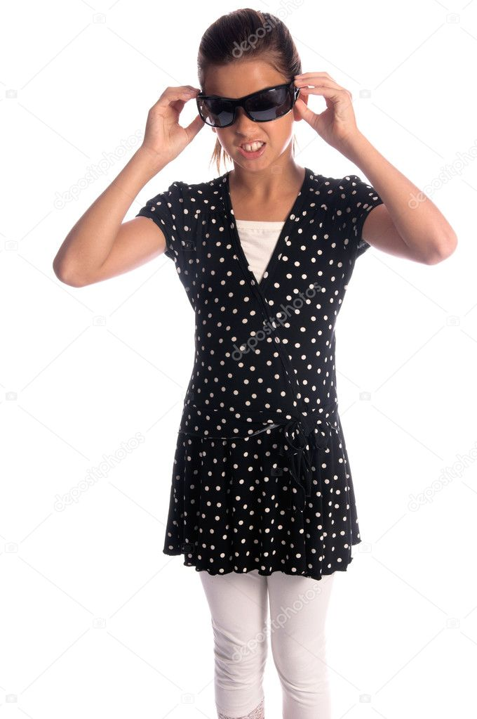 Pretty young girl (11 years old) in a black and white Polka dot dress and white leggins and super model sunglasses with a silly expression on her face — Stock Photo #6896421