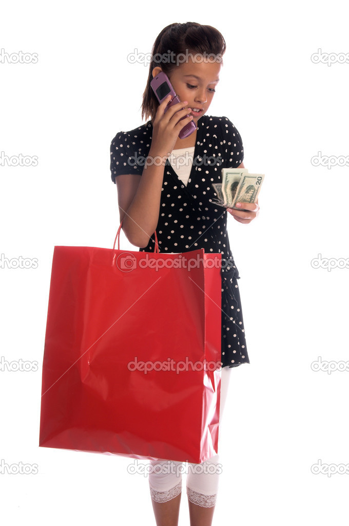 Twelve, 12 year old girl with a big red shopping bag and a handful of cash talking on a cell phone — Stock Photo #6896512