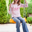 Young girl at swing chair in green environment — Stock Photo #7556352