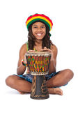 Rasta man sitting on the floor and beat a drum — Stock Photo