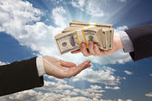 Handing Over Cash with Dramatic Clouds and Sky — Stock Photo