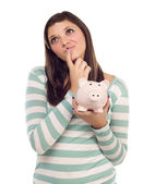 Ethnic Female Daydreaming and Holding Piggy Bank on White — Stock Photo