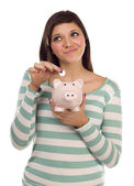 Ethnic Female Putting Coin Into Piggy Bank on White — Stock Photo