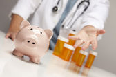 Doctor Reaches Palm Out Behind Medicine Bottles and Piggy Bank — Stock Photo