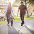 Happy Mixed Race Ethnic Family Walking In The Park — Stock Photo
