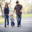Happy Mixed Race Ethnic Family Walking In The Park — Stock Photo #7678290