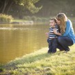 Royalty-Free Stock Photo: Happy Mother and Baby Son Looking Out At Lake