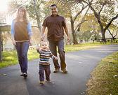 Família étnica de mestiços felizes andando no parque — Foto Stock