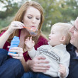 Stock Photo: Young Parents Blowing Bubbles with their Child Boy in Park