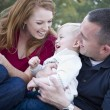 Attractive Young Parents Laughing with Child Boy in Park — Stock Photo #7902373